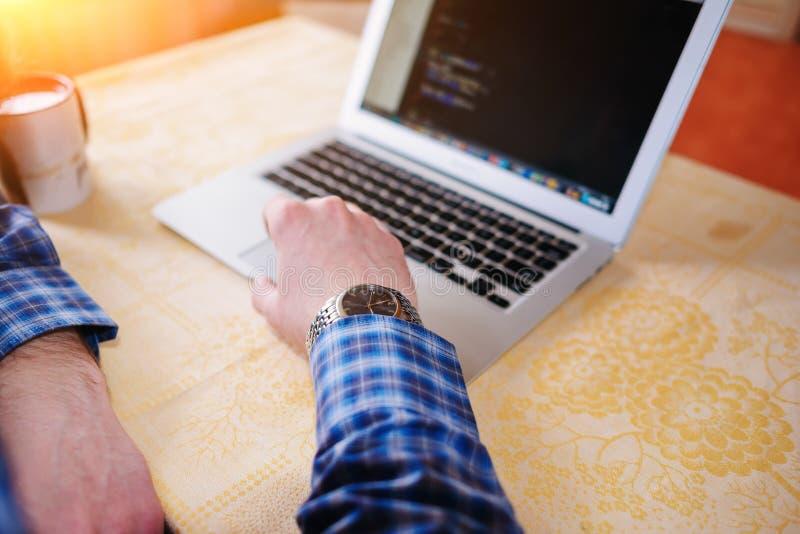 Entspannter junger Fachmann, der das Internet auf seinem Laptop in ein Esszimmer surft stockfotografie