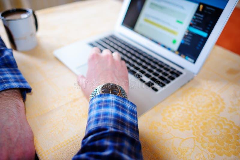 Entspannter junger Fachmann, der das Internet auf seinem Laptop in ein Esszimmer surft stockbilder