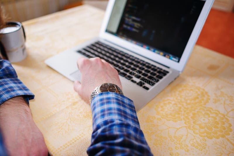 Entspannter junger Fachmann, der das Internet auf seinem Laptop in ein Esszimmer surft stockfotos