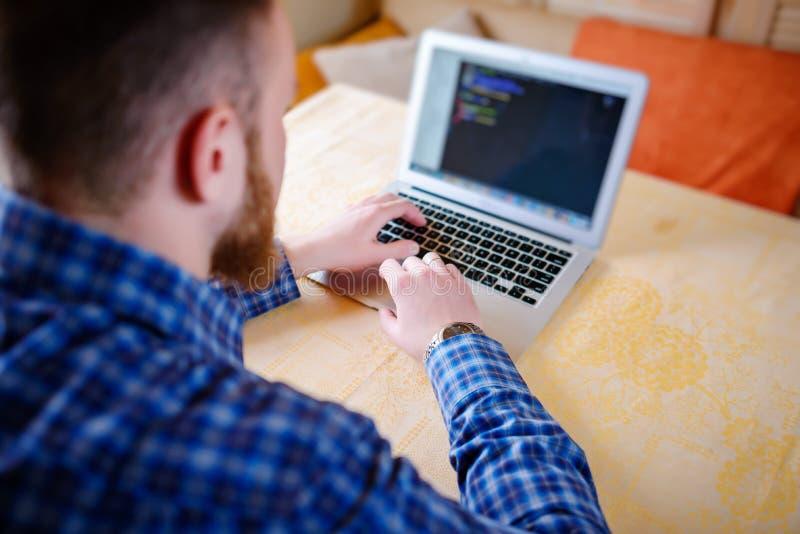 Entspannter junger Fachmann, der das Internet auf seinem Laptop in ein Esszimmer surft lizenzfreies stockfoto