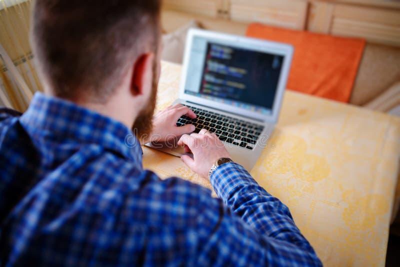 Entspannter junger Fachmann, der das Internet auf seinem Laptop in ein Esszimmer surft lizenzfreie stockbilder