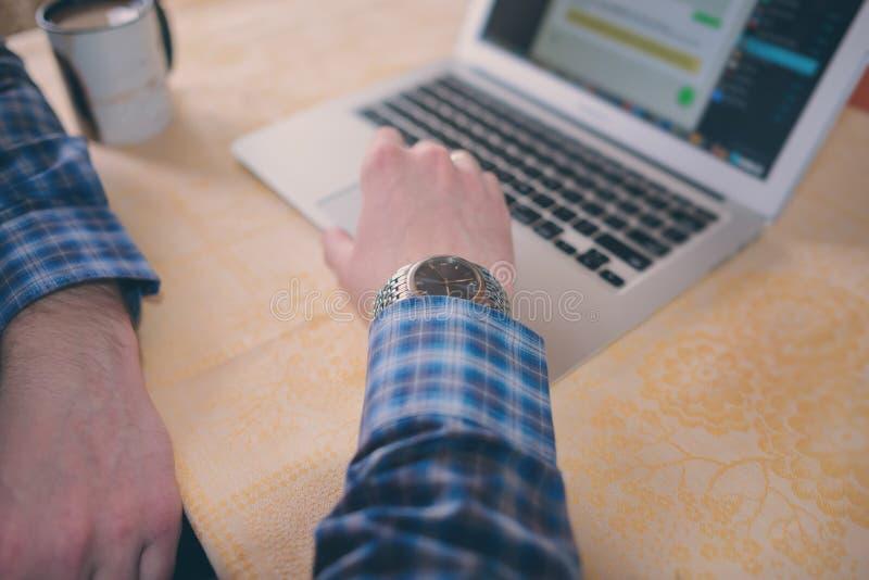 Entspannter junger Fachmann, der das Internet auf seinem Laptop in ein Esszimmer surft lizenzfreies stockbild