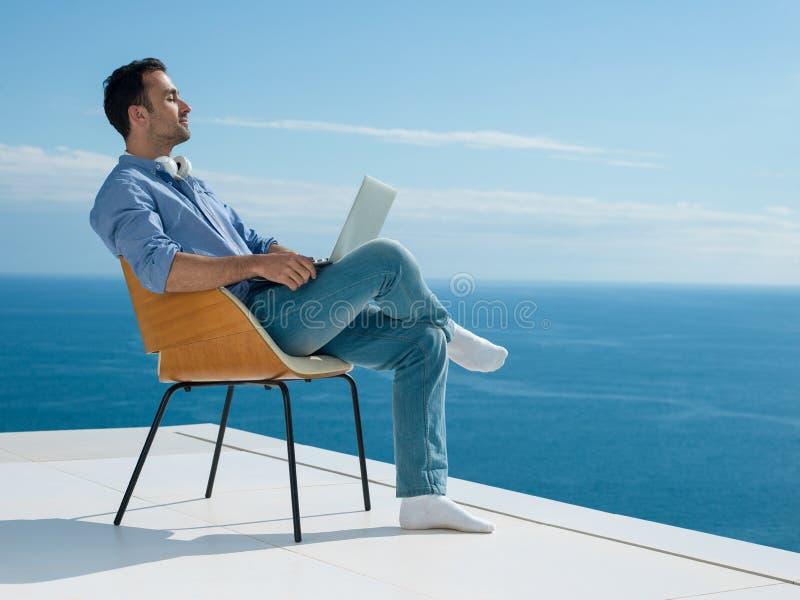 Entspannter junger Mann zu Hause auf Balkon lizenzfreie stockbilder