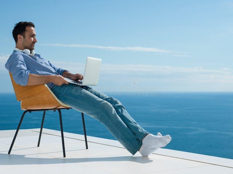 Entspannter junger Mann zu Hause auf Balkon stockbild