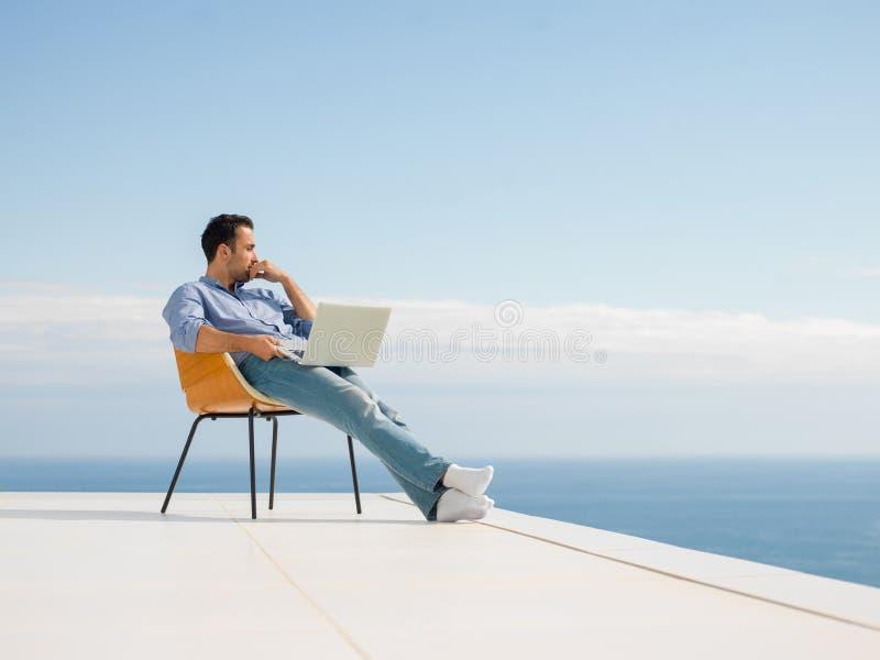Entspannter junger Mann zu Hause auf Balkon lizenzfreies stockbild