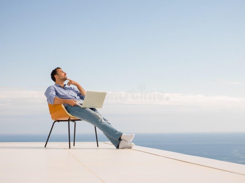 Entspannter junger Mann zu Hause auf Balkon lizenzfreie stockfotos