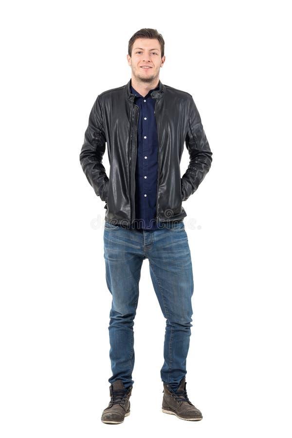 Entspannter Mann in den Jeans und in der Lederjacke lächelnd an der Kamera mit den Händen in den Taschen stockfoto