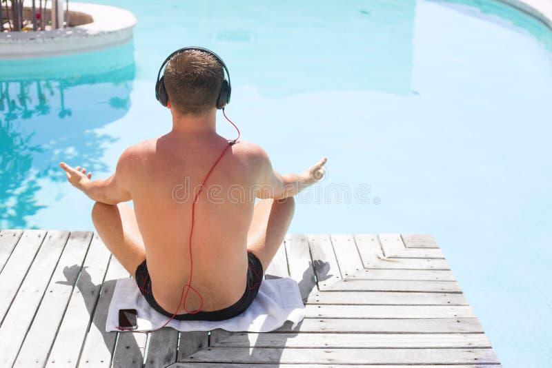 Entspannter Mann, der Musik auf Kopfhörern durch den Swimmingpool hört stockbild