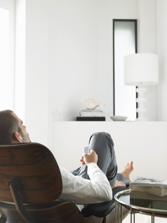 Entspannter Mann-hörende Musik auf MP3-Player stockbild