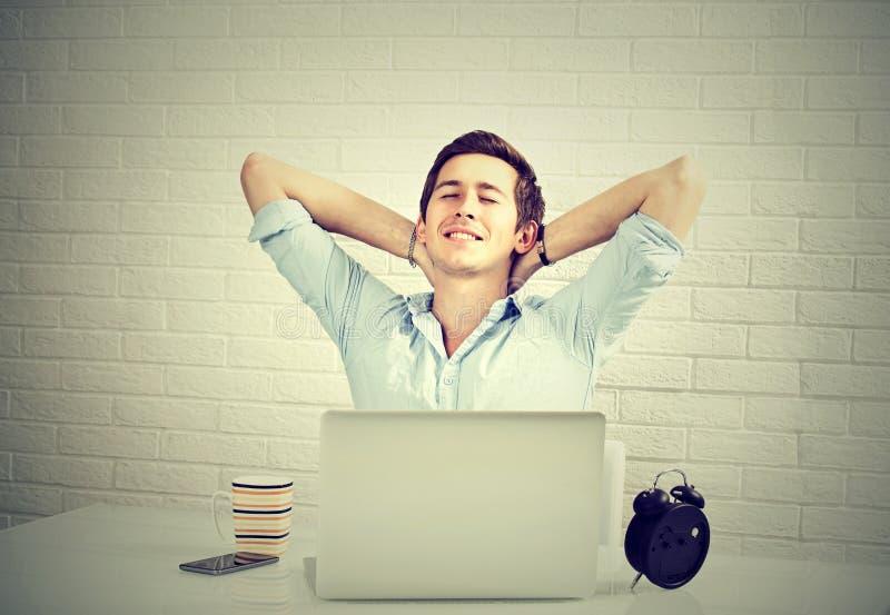 Entspannter Mann mit dem Laptop, der am Schreibtischbacksteinmauerhintergrund sitzt lizenzfreie stockfotografie