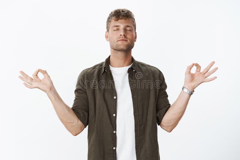 Entspannter meditierender Kerl mit Borste und angemessene Haarstellung in der Lotoshaltung im Suchnirwana, nahes Augenüben lizenzfreies stockfoto