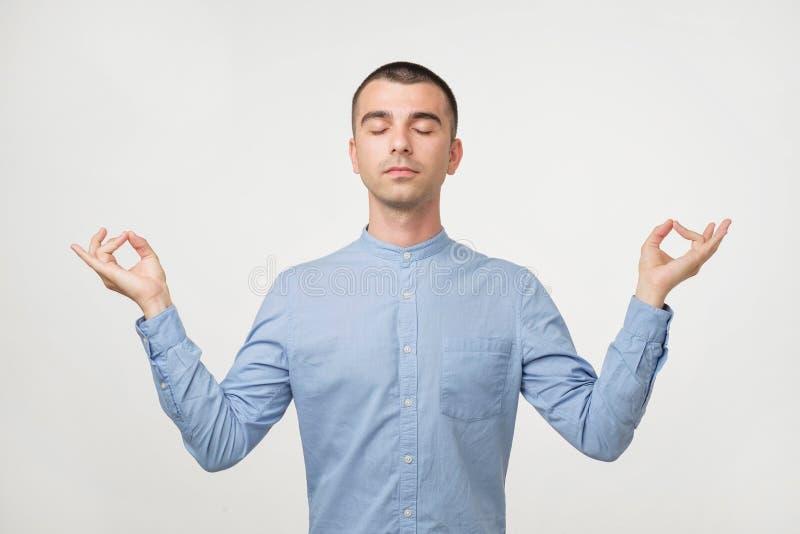 Entspannter sorgloser männlicher Student meditiert die Versuche, zum sich nach Überstunden des Studierens zu entspannen, sich kon lizenzfreie stockbilder