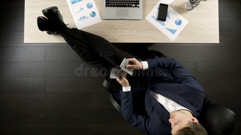 Entspannter wohlhabender Geschäftsmann, der das Geld, sitzend mit Füßen auf Tabelle, Draufsicht zählt lizenzfreies stockbild