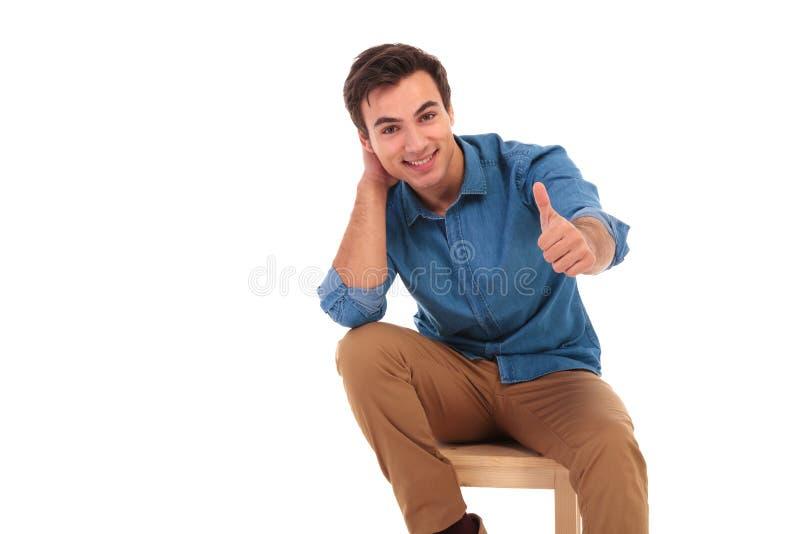 Entspannter zufälliger Sitzmann, der das okayzeichen macht stockfoto