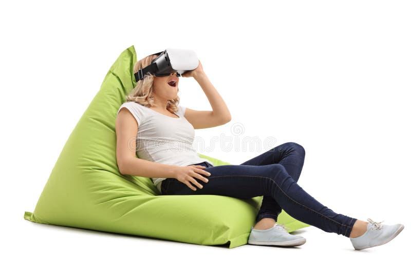 Entspanntes blondes Mädchen, das ein VR-Schutzbrillen verwendet stockbilder