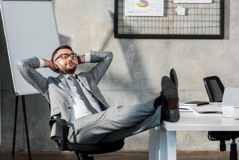 entspanntes buisnessman in den Brillen, die mit den Beinen auf Tabelle und Händen hinter Kopf sitzen lizenzfreie stockbilder