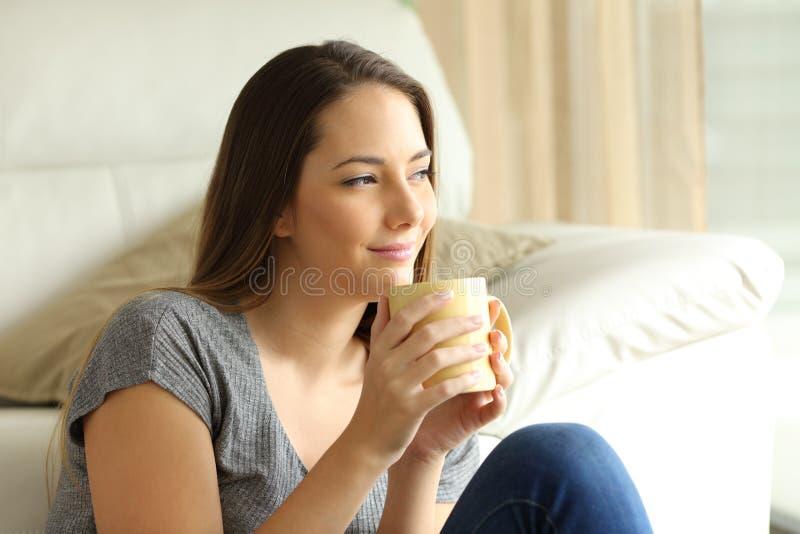 Entspanntes Mädchen, das mit einem Tasse Kaffee denkt lizenzfreie stockfotografie