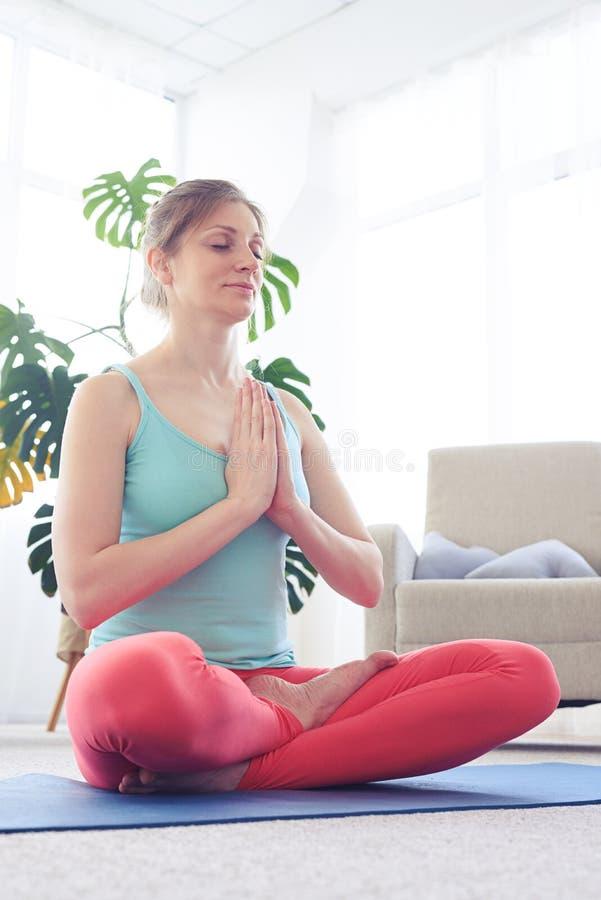 Entspanntes Mädchen in der Sportkleidung meditierend beim Sitzen auf Yogamatte stockfotografie