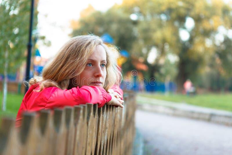 Entspannung der jungen Frau, das auf einem hölzernen Zaun sich lehnt lizenzfreie stockfotos