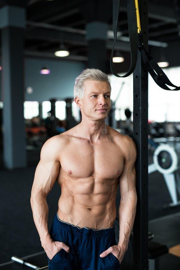 Entspannung durch pilates Kugel Muskulöser und sexy Torso des jungen Mannes, der perfekten sechs Satz-ABS, -bizeps und -kasten Bo stockbild