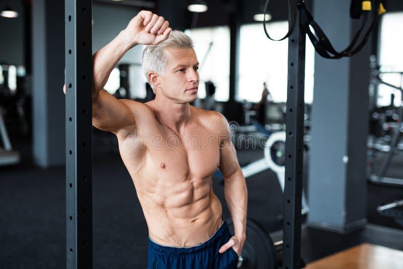 Entspannung durch pilates Kugel Muskulöser und sexy Torso des jungen Mannes, der perfekten sechs Satz-ABS, -bizeps und -kasten Bo stockfotos