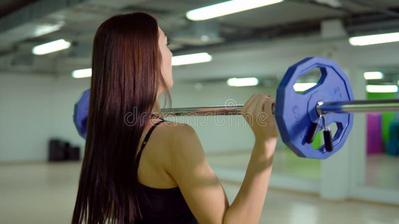Entspannung durch pilates Kugel Schöne Brunettefrau, die Übungen mit einem Barbell tut lizenzfreies stockbild