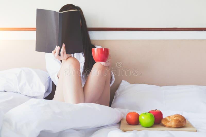 Entspannung morgens, das ein Buch liest und frühstückt stockfoto