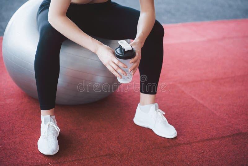 Entspannung nach der Ausbildung Ansicht der schönen jungen Frau, die beim Sitzen auf Übungsmatte Turnhalle weg betrachtet lizenzfreies stockbild