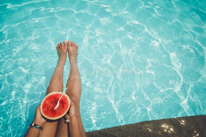 Entspannung und Freizeit - Lebensstil im Sommer von Tanned Mädchen tropische Frucht der Wassermelone im blauen Pool halten stockbilder