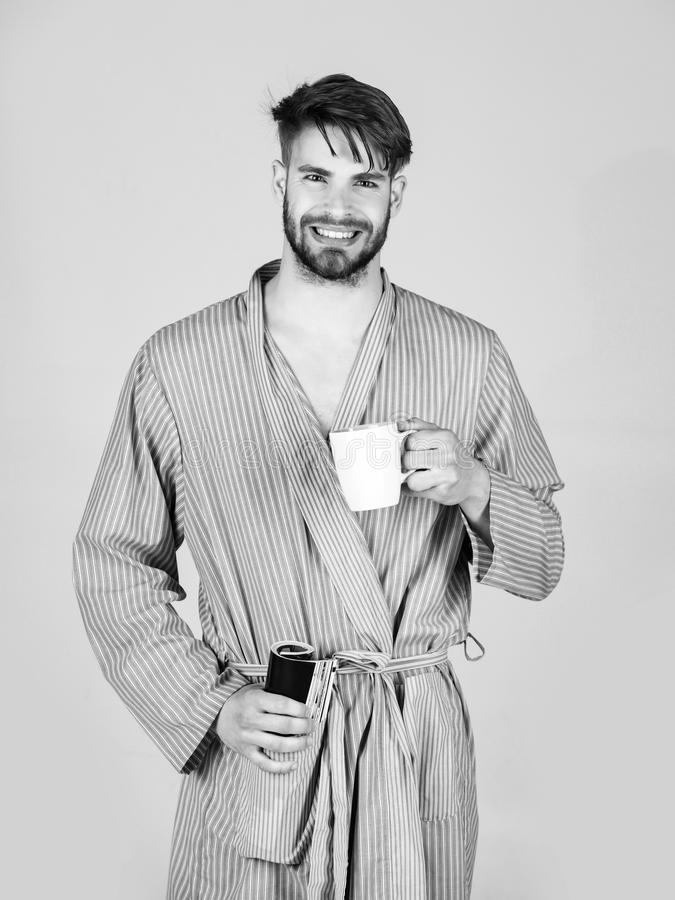 Entspannung und Freizeit Trinken und Lesen Glücklicher bärtiger Mann, der in der Robe mit Schale und Zeitschrift lächelt lizenzfreie stockbilder