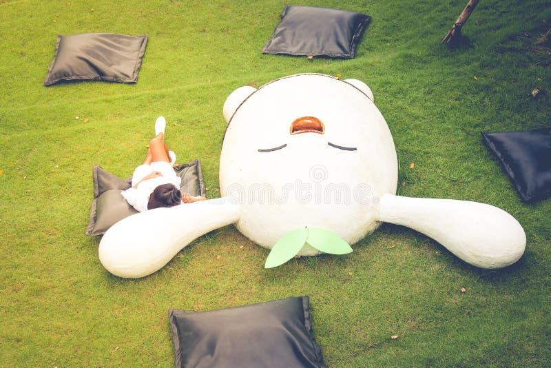 Entspannungs-Konzept: Draufsichtfrau, die auf schwarzem Kissen und grünem Gras Garten am im Freien liegt stockfotos