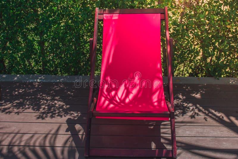 Entspannungs-Konzept: Rote hölzerne Daybedeinstellung auf Bretterboden neben Swimmingpool am Erholungsort lizenzfreie stockfotos