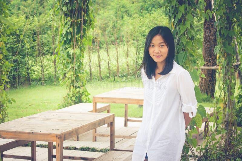 Entspannungs-Konzept: Weißes Hemd der Asiatinabnutzung, das auf Gras Garten am im Freien steht und mit der Entspannung lächelt lizenzfreie stockfotos