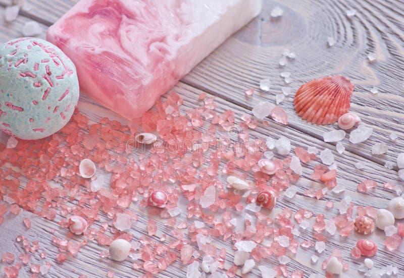 Entspannungs- und Behandlungshintergrund mit Badebombe, handgemachter Stück Seife, Muscheln und Aromatherapiesalz lizenzfreie stockbilder