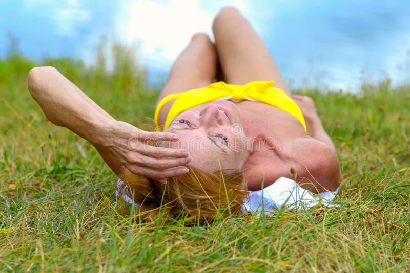 Entspannungsc$ein sonnenbad nehmen der Frau auf dem Gras stockbilder