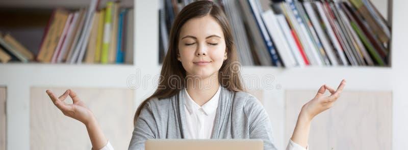 Entspannungsc$meditieren der horizontalen Fotofrau am Arbeitsplatz während des Arbeitstages stockfoto