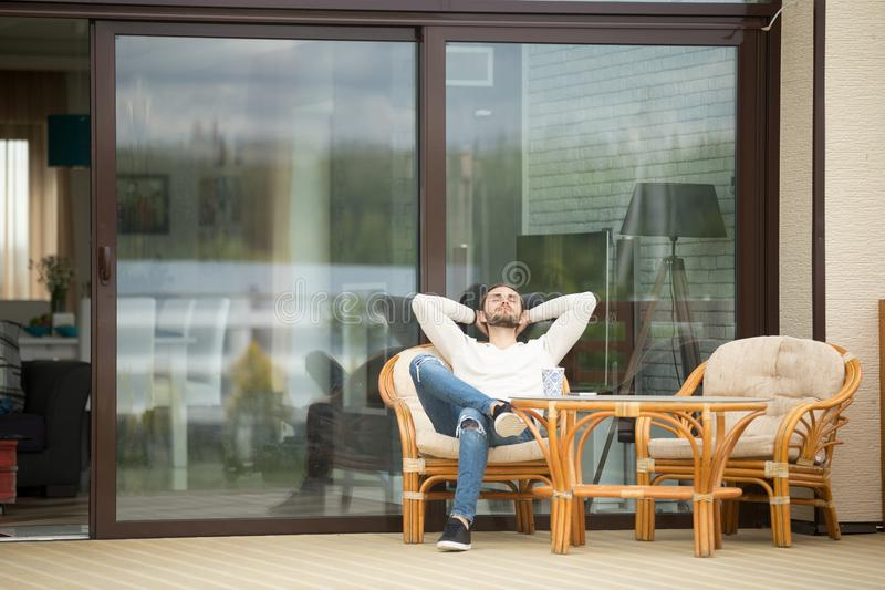 Entspannungsc$sitzen des jungen Mannes auf Terrassenstuhl, atmende Frischluft stockbilder