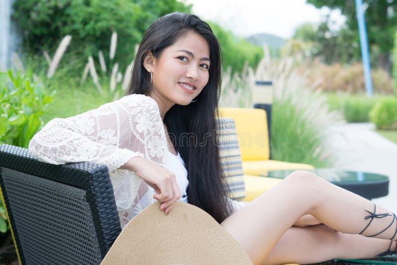 Entspannungsfrauensitzen bequem beim Sofaklubsessellächeln glücklich lizenzfreie stockfotos