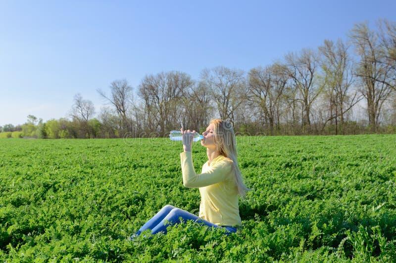 Entspannungsgetränke der jungen Frau wässern von einer Plastikflasche stockbilder