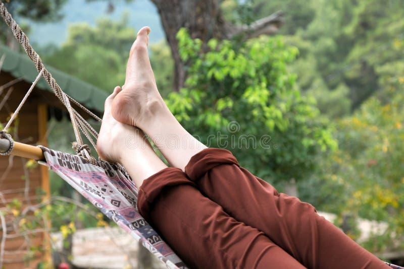Entspannungslügen der Person in der Hängematte am ländlichen Häuschengarten lizenzfreie stockfotos
