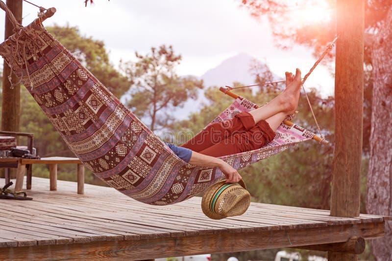 Entspannungslügen der Person in der Hängematte am ländlichen Häuschengarten lizenzfreies stockfoto