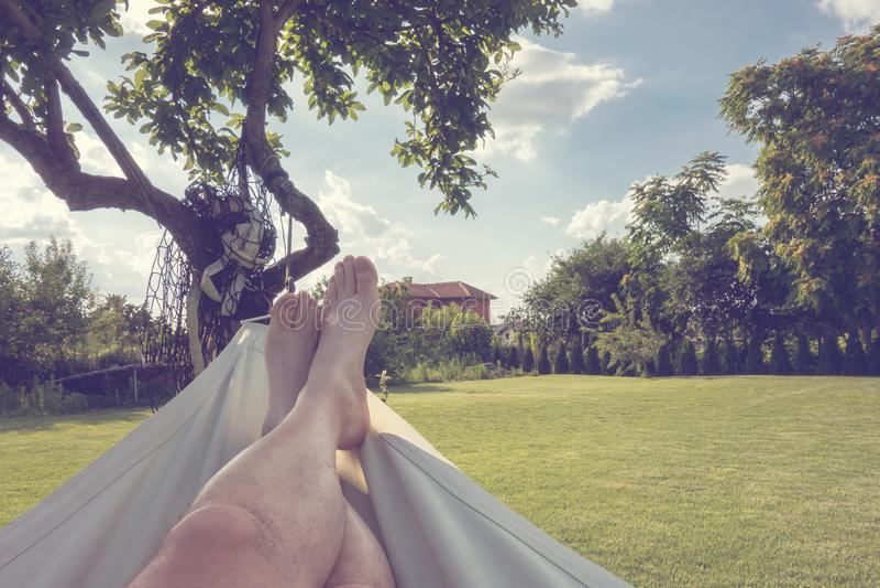 Entspannungslügen der Person in der Hängematte im Sommergarten lizenzfreies stockbild