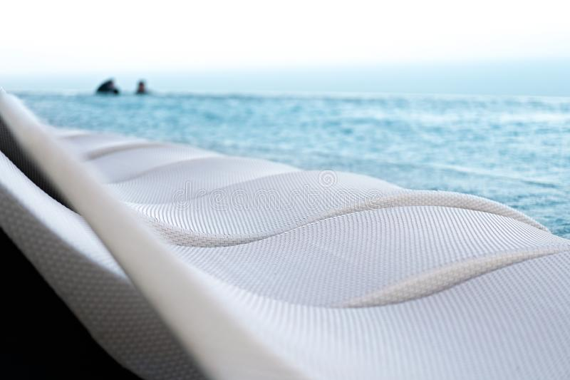 Entspannungspoolbett neben Swimmingpool lizenzfreies stockfoto