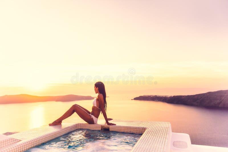 Entspannungssich hinlegen der vorbildlichen Frau des Luxus-Resort-Ferienbikinis durch Swimmingpoolhotelzimmerreihenbalkon des Jac stockfoto