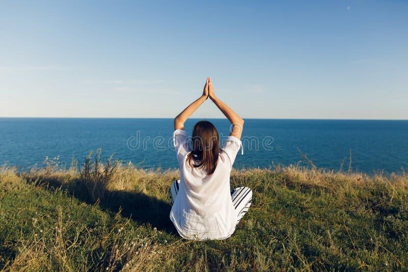 Entspannungsund übendes Yoga der jungen Schönheit auf Strand, sitzend im Gras, meditieren und hören auf Meereswellen Druck für Ih stockfotos