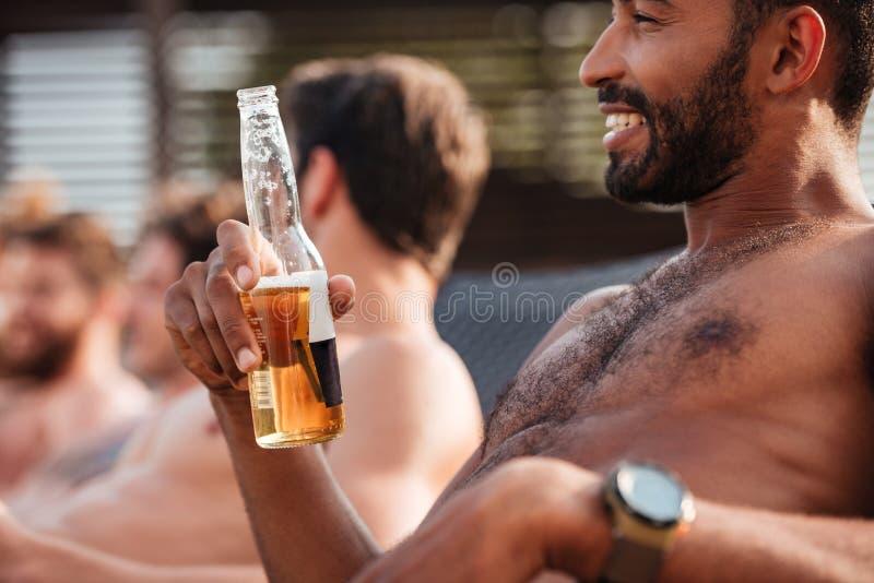 Entspannungsund trinkendes Bier des glücklichen afrikanischen Mannes mit Freunden lizenzfreie stockfotografie
