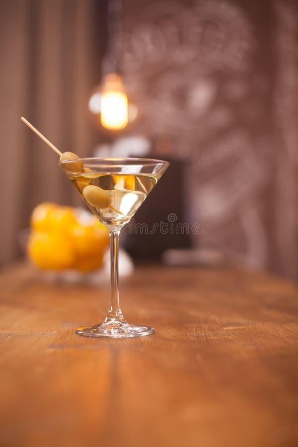Entspannungszeit im Restaurant mit einem Glas Martini und grünen Oliven lizenzfreies stockfoto