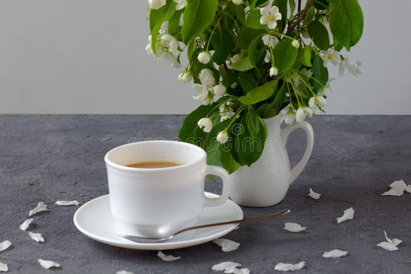Entspannungszeit und Glück mit Tasse Kaffee mit unter frischer Frühlingsblume lizenzfreie stockfotos
