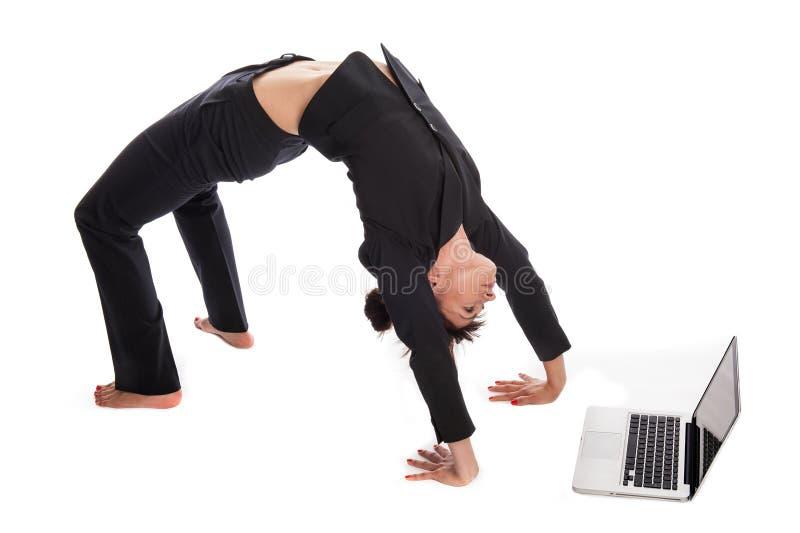 Entsprochene Frau in der Yoga-Haltung, die mit Laptop arbeitet. stockfoto