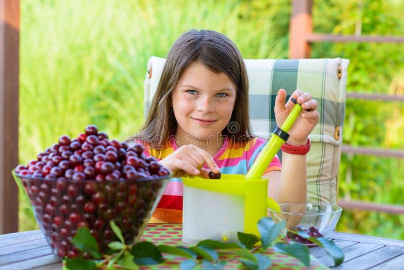 Entsteinen von frischen Kirschen durch junges hübsches Mädchen im Garten stockfotos